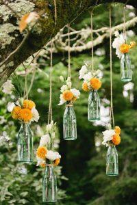 botellas con flores colgando de un cordel