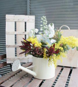 regadera con flores silvestres